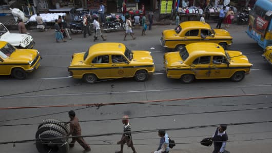 Taxis sit in traffic on a street in Kolkata, India.