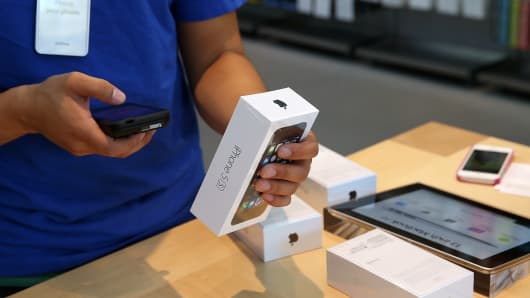 An Apple Store employee rings up a purchase of the new iPhone 5S in Palo Alto, California.