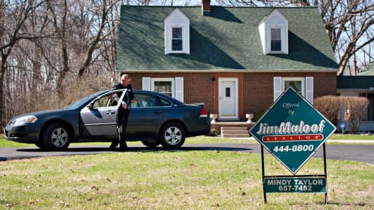 An agent with Jim Maloof Realtors, checks his mobile phone as he arrives outside a home for sale in East Peoria, Illinois, April 18, 2014.