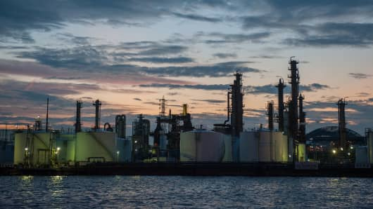 Tanks and stacks stand at a refinery at dusk in the Keihin Industrial Area of Kawasaki City, Kanagawa Prefecture, Japan.