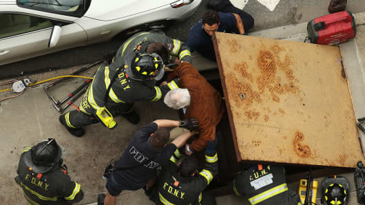New York City firefighters use an emergency staircase to evacuate passengers from a derailed F train on May 2, 2014 in the Woodside neighborhood of the Queens borough of New York City.