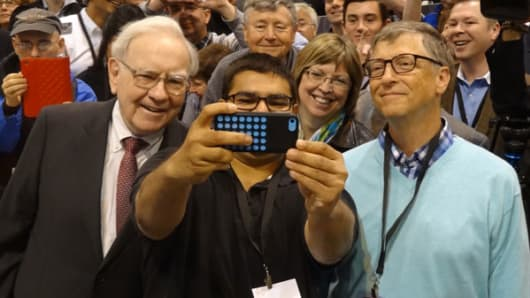 Warren Buffett and Berkshire Hathaway board member Bill Gates participate in a fan's selfie at the company's annual meeting on May 3, 2014.