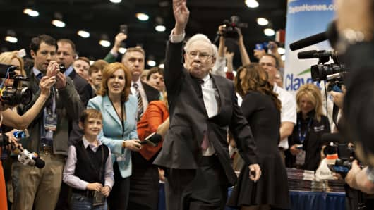 Warren Buffett, chairman of Berkshire Hathaway Inc., tosses a newspaper as he tours the exhibition floor prior to the Berkshire Hathaway shareholders meeting.