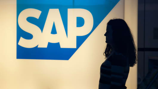 A visitor passes an illuminated SAP AG logo inside the business software maker's headquarters in Walldorf, Germany.
