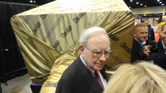 Warren Buffett stands next to a 7000 pound chocolate lollipop at the 2014 Berkshire Hathaway Annual Shareholder's Meeting in Omaha, Nebraska.
