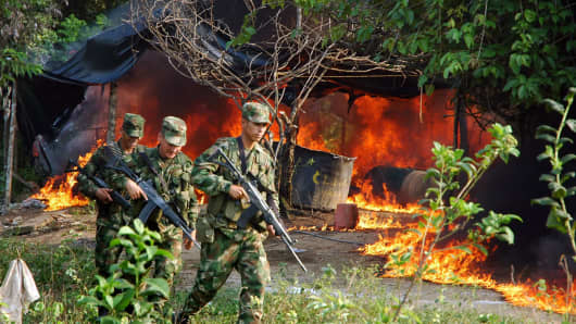 Colombian soldiers leave the place after setting on fire a cocaine processing laboratory