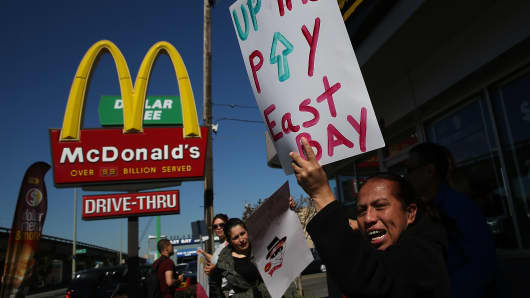 Fast food workers and activists protest outside of a McDonald's restaurant on March 18, 2014 in Oakland, California.