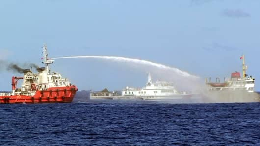 In this photo released by Vietnam Coast Guard, a Chinese ship, left, shoots water cannon at a Vietnamese vessel, right, while a Chinese Coast Guard ship, center, sails alongside in the South China Sea, off Vietnam's coast, Wednesday, May 7, 2014.