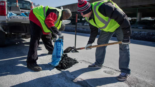 Members of the Boston Public Works Department fill potholes.