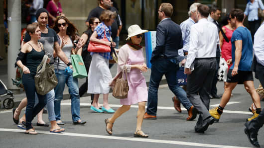 City shoppers cross a busy intersection in central Sydney.