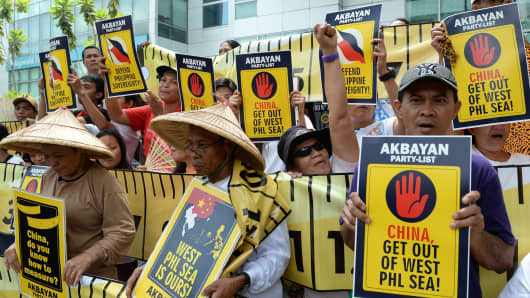 Protesters hold anti-China placards and shout slogans during a rally in front of the building housing Chinese consular offices in Manila.