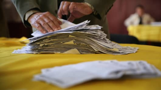An election official sorts through a pile of 'yes' votes for independence for eastern Ukraine.