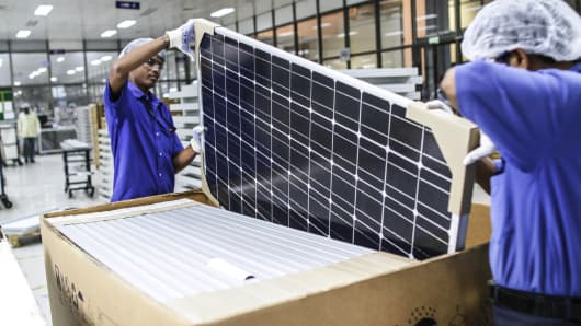 Employees place a solar panel into a box at the Tata Power Solar Systems manufacturing plant in Bangalore, India.