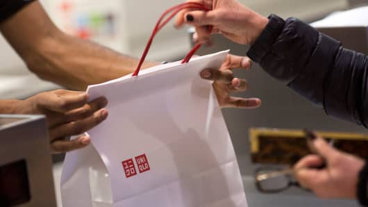 An employee hands a bag to a customer at a Uniqlo store in New York, Jan. 21, 2014.