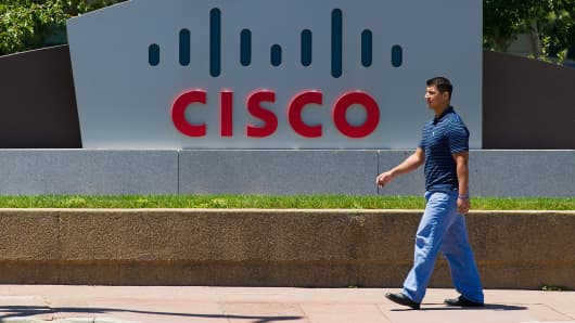 A pedestrian walks past Cisco Systems Inc. signage