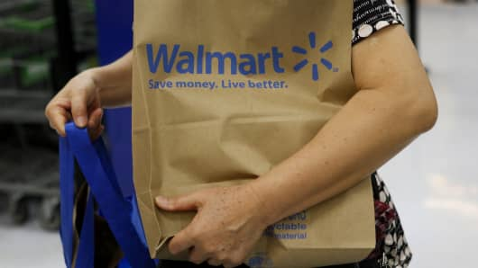 A customer carries a Walmart paper shopping bag during the grand opening of a Wal-Mart Stores Inc. location in the Chinatown neighborhood of Los Angeles, California.