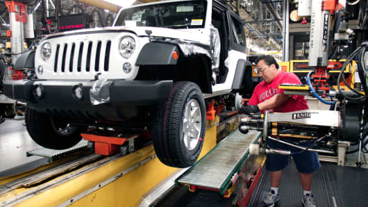 A worker installs tires on a 2014 Jeep Wrangler as it undergoes assembly at the Chrysler Toledo North Assembly Plant, May 7, 2014 in Toledo, Ohio.