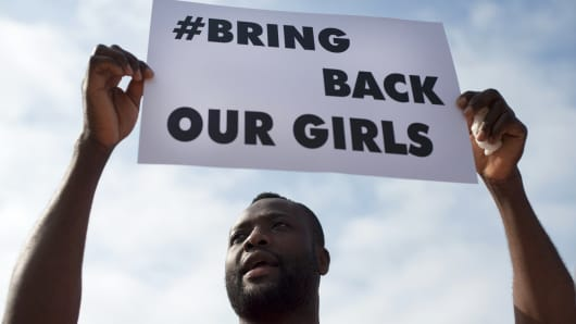 A man holds a placard reading 'Bring Back Our Girls' to denounce the kidnapping of more than 200 Nigerian schoolgirls by Islamic militants on May 13 , 2014 in Malaga.