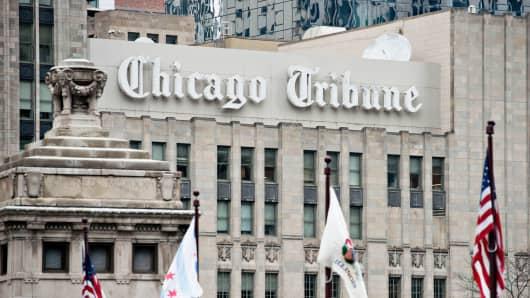Flags fly in front of Chicago Tribune signage displayed on the side of the Tribune Tower in Chicago, March 28, 2014.
