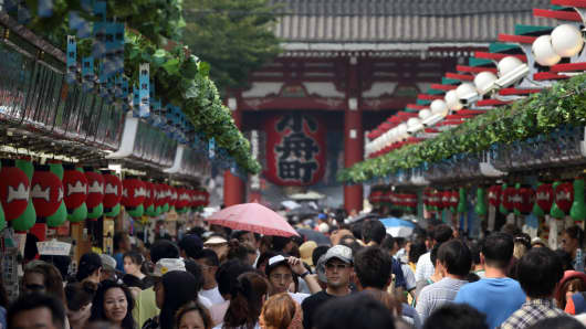Shoppers and tourists walk through a shopping street in front of the Sensoji temple in Tokyo, Japan.