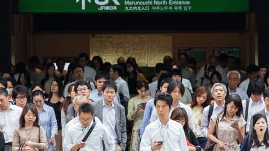 Morning commuters wait to cross a street in front of Tokyo Station in Tokyo, Japan.
