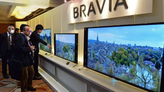 Journalists look at Japanese electronics maker Sony's new 4K television set line up at a press preview in Tokyo.