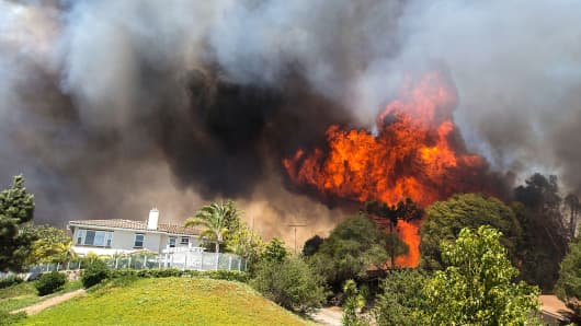 Flames near a house in Carlsbad, Calif., May 14, 2014.