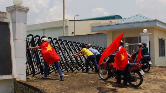 Protesters holding Vietnamese flags attempt to push down the front gate of a factory in Bien Hoa, Dong Nai province.