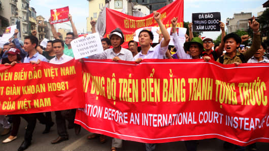 Anti-China protesters march while shouting slogans in front of the Chinese embassy during a rally in Hanoi.