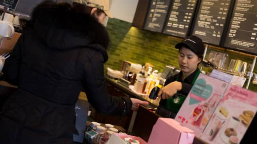 A barista scans a barcode on a customer's smartphone at a Starbucks.