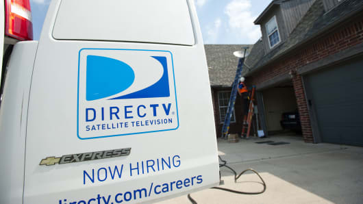 A DirecTV employee performs a satellite installation at a customer's home in Bixby, Oklahoma.