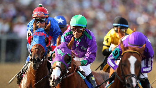 California Chrome #3, ridden by Victor Espinoza, races with the field during the 139th running of the Preakness Stakes at Pimlico Race Course on May 17, 2014 in Baltimore.