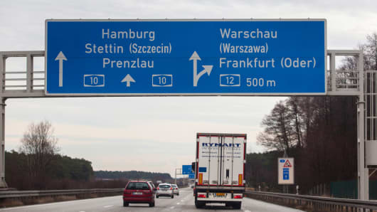 Automobiles and a freight truck pass under a road traffic junction sign on the Berliner Ring road near Zernsdorf, Germany, on Thursday, Jan. 9, 2014.