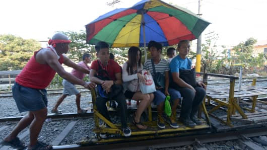People riding on a makeshift trolley that is pushed on the rails of the Philippine railroad in Manila.