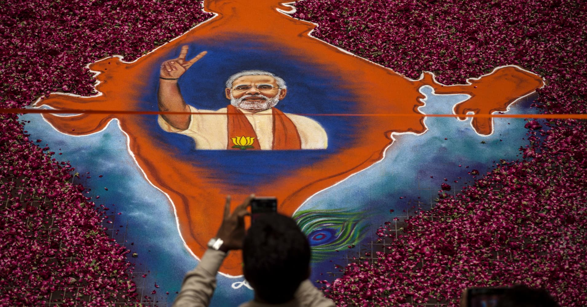 A supporter takes a picture of a map of India made of flowers with a picture of BJP leader Narendra Modi on it at the party's headquarters.