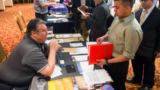Bob Truncali of DeVry College, left, talks with job seeker James Echeverry of Queens at a career fair in New York, May 13, 2014.