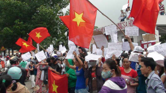 Protesters wave flags and hold placards on a street outside a factory building in Binh Duong.