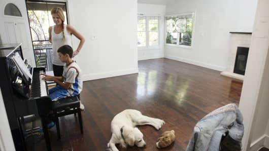 Jenna Dillon-Gasparino, her son, William, and Rocky the dog in their house, which is on the market for sharply more than the family bought it for, just four years ago, in the Venice neighborhood of Los Angeles, May 19, 2014. In some markets, buying a house again looks like a perilous investment.