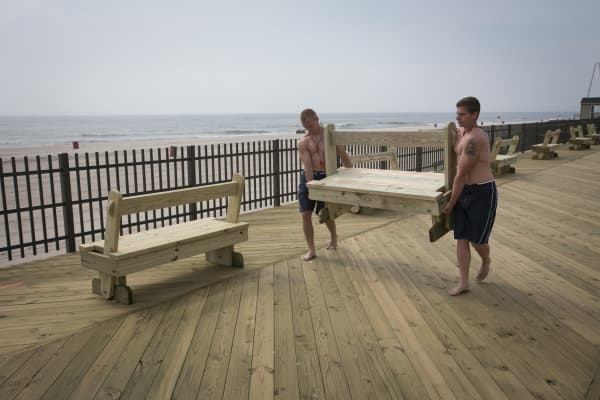 Members of the beach patrol help place new benches along the boardwalk in Seaside Heights, New Jersey.