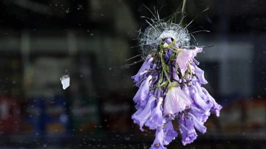 Flowers are placed through a bullet hole on a window of IV Deli Mart, where part of Friday night's mass shooting took place by a drive-by shooter, on Saturday, May 24, 2014, in Isla Vista, Calif. Sheriff's officials say Elliot Rodger, 22, went on a rampage near the University of California, Santa Barbara, stabbing three people to death at his apartment before shooting and killing three more in a crime spree through a nearby neighborhood.