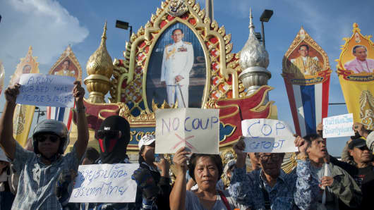 Anti-coup protesters hold banners in front of portraits of Thai King Bhumibol Adulyadej during a demonstration at Victory Monument in Bangkok, Thailand.