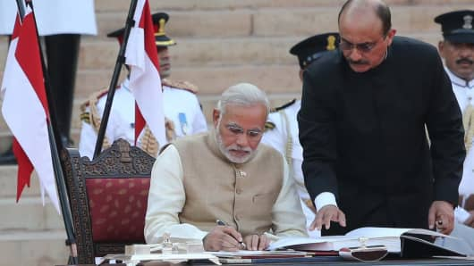 Narendra Modi (L), became India's 15th prime minister on Monday, taking his oath in front of 4000 guests at the Presidential Palace in New Delhi.