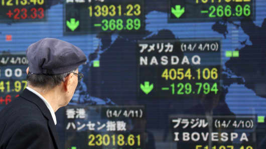 A pedestrian walks past an electronic stock board displaying a mid-day figure of the Nikkei 225 Stock Average outside a securities firm in Tokyo, Japan.