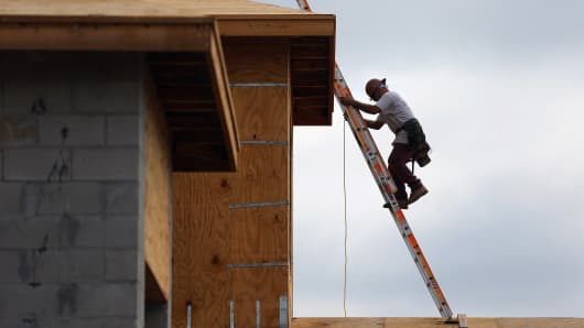 A construction worker climbs on the roof of a home in Boca Raton, Florida.