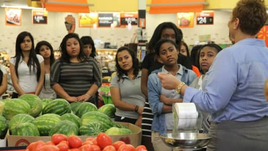 Students from Scarborough High School listen to a Houston-area Walmart manager talk about how to source produce.