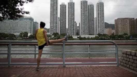 A man exercises in front of residential buildings along the Shing Mun River in the Sha Tin area of Hong Kong, China.