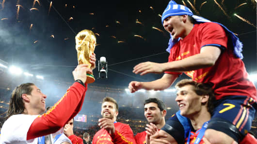 Spain's defender Sergio Ramos (L) hands the trophy to Spain's striker David Villa (top) as Spain's national soccer team players celebrate winning the 2010 World Cup final at Soccer City stadium in Soweto, suburban Johannesburg.