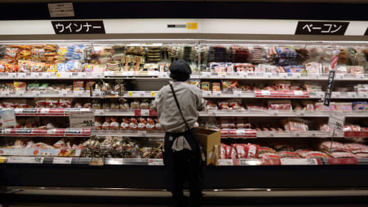 An employee arranges a display of sausages, left, and bacon, right, at an Aeon Co. supermarket in Chiba, Japan.