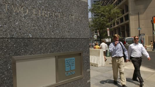 Pedestrians walk past the entrance to the Cigna Corp. headquarters in Philadelphia, Pennsylvania.