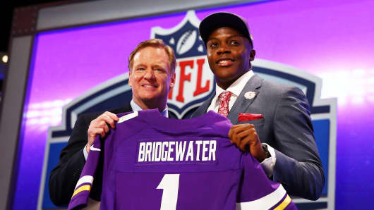 Teddy Bridgewater of the Louisville Cardinals poses with NFL Commissioner Roger Goodell after he was picked #32 overall by the Minnesota Vikings during the first round of the 2014 NFL Draft at Radio City Music Hall on May 8, 2014 in New York City.